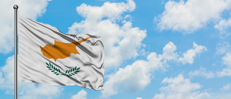 Cyprus flag waving in the wind against white cloudy blue sky. Diplomacy concept, international relations.