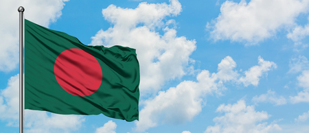 Bangladesh flag waving in the wind against white cloudy blue sky. Diplomacy concept, international relations. Foto de archivo
