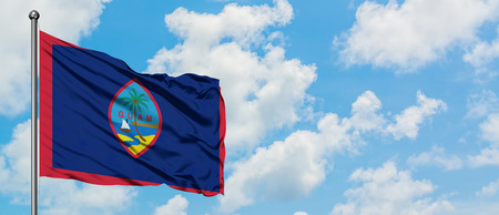 Guam flag waving in the wind against white cloudy blue sky. Diplomacy concept, international relations. Stock Photo