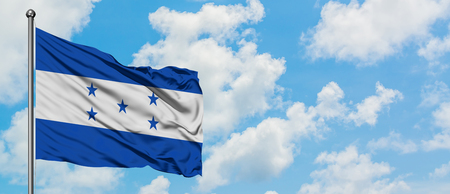 Honduras flag waving in the wind against white cloudy blue sky. Diplomacy concept, international relations.