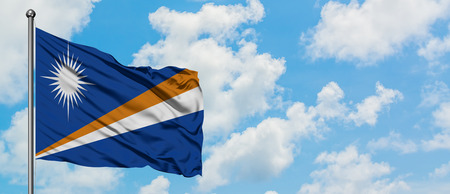 Marshall Islands flag waving in the wind against white cloudy blue sky. Diplomacy concept, international relations.