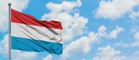 Luxembourg flag waving in the wind against white cloudy blue sky. Diplomacy concept, international relations.