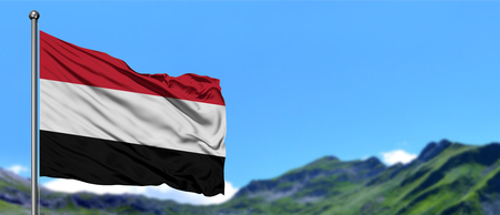 Yemen flag waving in the blue sky with green fields at mountain peak background. Nature theme.