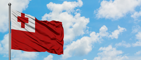 Tonga flag waving in the wind against white cloudy blue sky. Diplomacy concept, international relations.