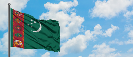 Turkmenistan flag waving in the wind against white cloudy blue sky. Diplomacy concept, international relations.