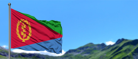 Eritrea flag waving in the blue sky with green fields at mountain peak background. Nature theme. Foto de archivo