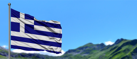 Greece flag waving in the blue sky with green fields at mountain peak background. Nature theme. Stockfoto