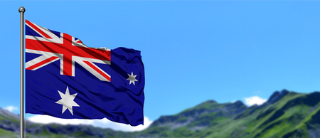 Heard Island and Mcdonald Islands flag waving in the blue sky with green fields at mountain peak background. Nature theme.