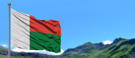 Madagascar flag waving in the blue sky with green fields at mountain peak background. Nature theme.