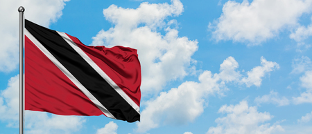 Trinidad And Tobago flag waving in the wind against white cloudy blue sky. Diplomacy concept, international relations.