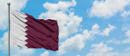 Qatar flag waving in the wind against white cloudy blue sky. Diplomacy concept, international relations.