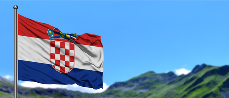 Croatia flag waving in the blue sky with green fields at mountain peak background. Nature theme. 免版税图像