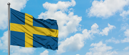Sweden flag waving in the wind against white cloudy blue sky. Diplomacy concept, international relations.