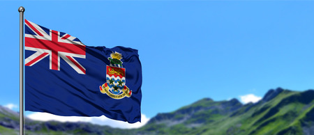 Cayman Islands flag waving in the blue sky with green fields at mountain peak background. Nature theme.