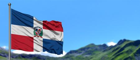 Bandera de República Dominicana ondeando en el cielo azul con campos verdes en el fondo del pico de la montaña. Tema de la naturaleza.