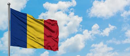 Bandera de Rumania ondeando en el viento contra el cielo azul nublado blanco. Concepto de diplomacia, relaciones internacionales.