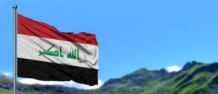 Iraq flag waving in the blue sky with green fields at mountain peak background. Nature theme.