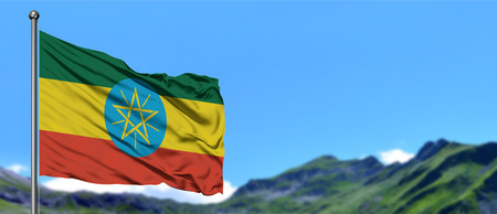 Ethiopia flag waving in the blue sky with green fields at mountain peak background. Nature theme.