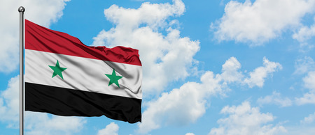 Syria flag waving in the wind against white cloudy blue sky. Diplomacy concept, international relations. Imagens