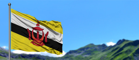 Brunei flag waving in the blue sky with green fields at mountain peak background. Nature theme. Foto de archivo