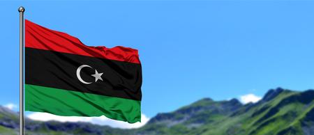 Bandiera della Libia che sventola nel cielo blu con campi verdi sullo sfondo del picco di montagna. Tema della natura. Archivio Fotografico