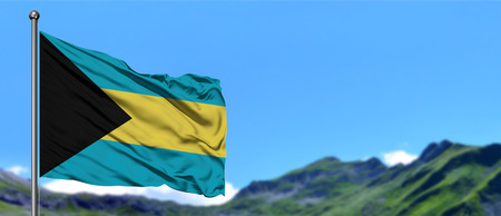 Bahamas flag waving in the blue sky with green fields at mountain peak background. Nature theme.