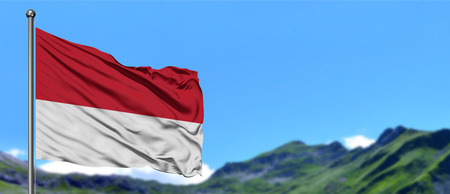 Monaco flag waving in the blue sky with green fields at mountain peak background. Nature theme.