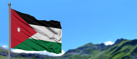 Jordan flag waving in the blue sky with green fields at mountain peak background. Nature theme.