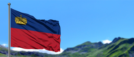 Liechtenstein flag waving in the blue sky with green fields at mountain peak background. Nature theme. Stock Photo