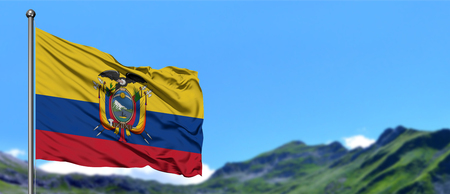 Ecuador flag waving in the blue sky with green fields at mountain peak background. Nature theme. Banco de Imagens
