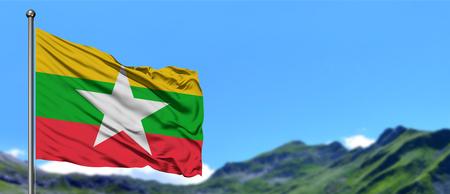 Bandiera del Myanmar che sventola nel cielo blu con campi verdi sullo sfondo del picco di montagna. Tema della natura.