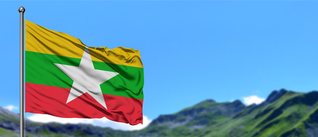 Myanmar flag waving in the blue sky with green fields at mountain peak background. Nature theme. Stock Photo