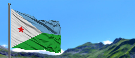 Djibouti flag waving in the blue sky with green fields at mountain peak background. Nature theme.