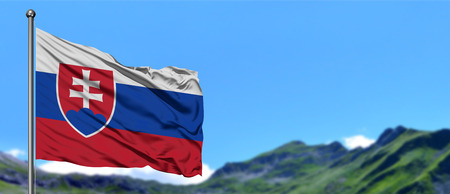 Slovakia flag waving in the blue sky with green fields at mountain peak background. Nature theme.