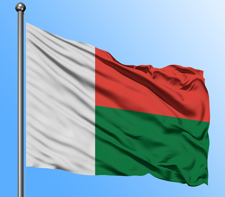 Madagascar flag waving in the deep blue sky background. Isolated national flag. Macro view shot.