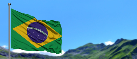 Brazil flag waving in the blue sky with green fields at mountain peak background. Nature theme.