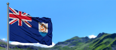 Anguilla flag waving in the blue sky with green fields at mountain peak background. Nature theme. Foto de archivo
