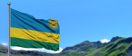 Rwanda flag waving in the blue sky with green fields at mountain peak background. Nature theme.