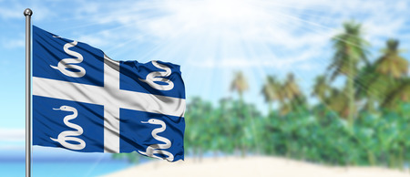 Waving Martinique flag in the sunny blue sky with summer beach background. Vacation theme, holiday concept. Foto de archivo