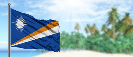 Waving Marshall Islands flag in the sunny blue sky with summer beach background. Vacation theme, holiday concept.