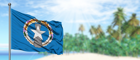 Waving Northern Mariana Islands flag in the sunny blue sky with summer beach background. Vacation theme, holiday concept.