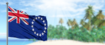 Waving Cook Islands flag in the sunny blue sky with summer beach background. Vacation theme, holiday concept.