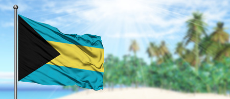 Waving Bahamas flag in the sunny blue sky with summer beach background. Vacation theme, holiday concept. Stock Photo