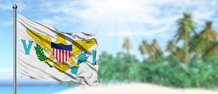Waving United States Virgin Islands flag in the sunny blue sky with summer beach background. Vacation theme, holiday concept.