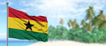 Waving Ghana flag in the sunny blue sky with summer beach background. Vacation theme, holiday concept.