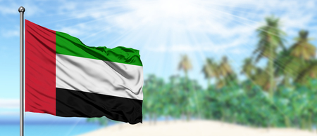 Waving United Arab Emirates flag in the sunny blue sky with summer beach background. Vacation theme, holiday concept.