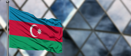 Azerbaijan flag waving in the wind against blurred modern building. Business concept. National cooperation theme. Foto de archivo