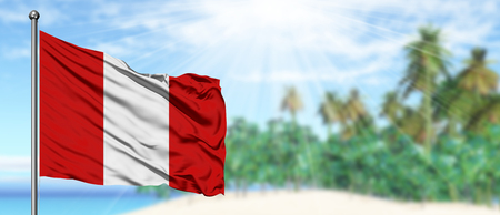 Waving Peru flag in the sunny blue sky with summer beach background. Vacation theme, holiday concept.