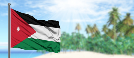 Waving Jordan flag in the sunny blue sky with summer beach background. Vacation theme, holiday concept.