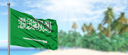 Waving Saudi Arabia flag in the sunny blue sky with summer beach background. Vacation theme, holiday concept.